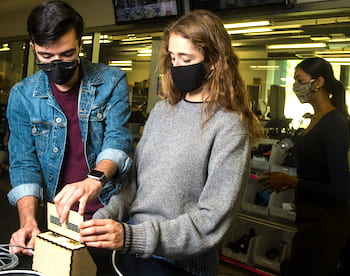 Rice University engineering students have designed a low-cost touchless temperature monitor. Diego Gonzalez and Caterina Grasso Goebel make an adjustment to the temperature readout, attached by a long cable to the sensor to keep people at a distance. (Credit: Photo by Jeff Fitlow/Rice University)