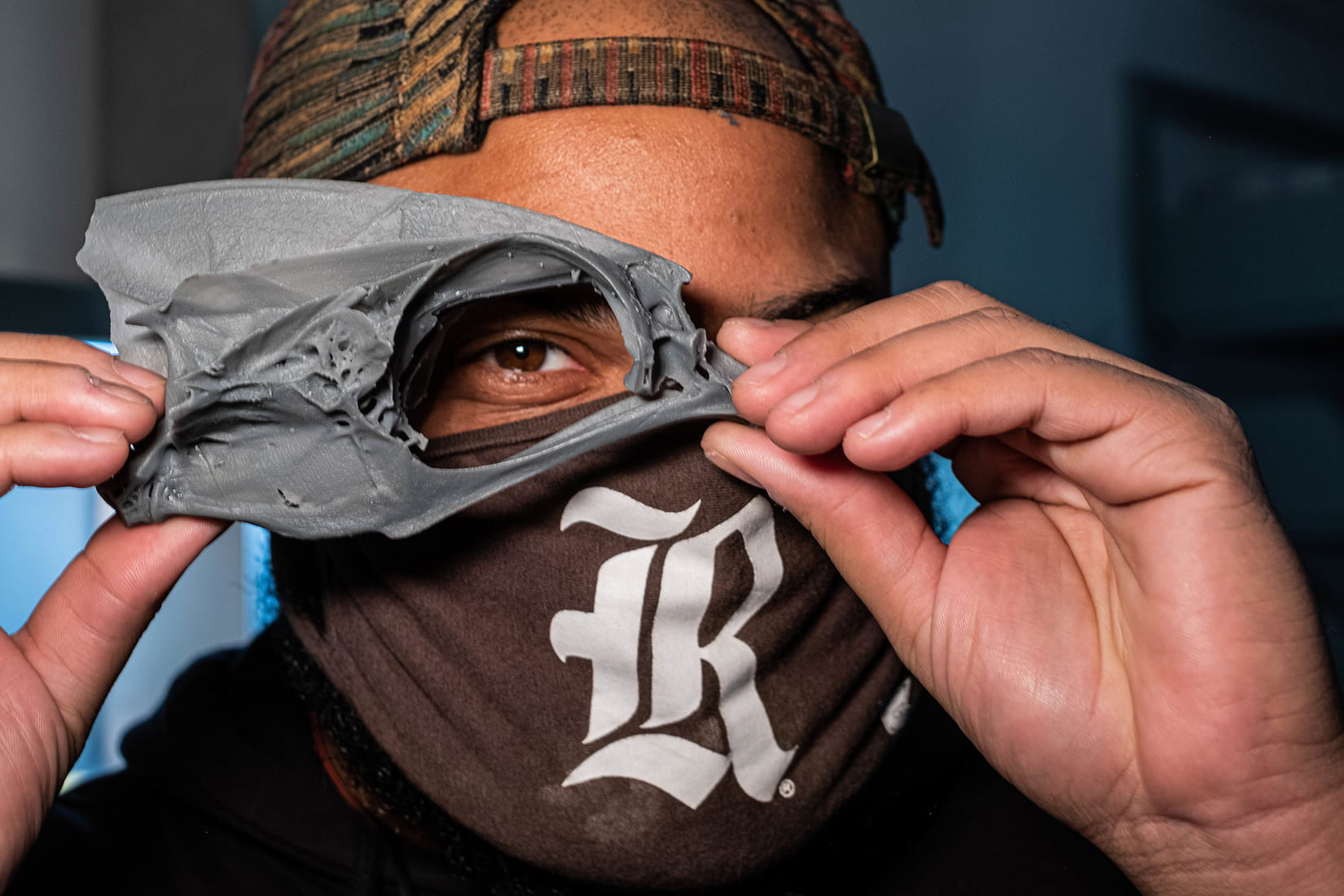 person in backward cap and mask holds 3D printed skull up to peek through it