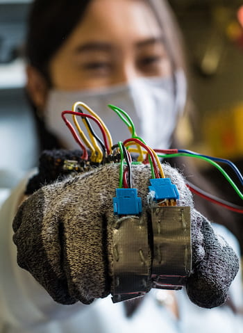 Rice University graduate student Linda Liu models the prototype glove to help reward the positive behaviors of people with trichotillomania, the compulsive pulling of hair. Photo by Jeff Fitlow