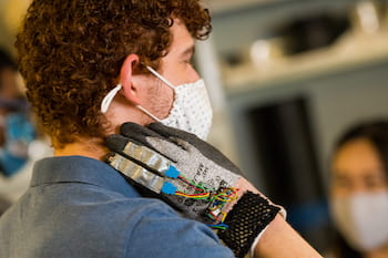 Rice University engineering student Zach Alvear tests the prototype glove developed to monitor the hand motions of people with trichotillomania, the compulsive pulling of hair, to help them modify their behavior. (Credit: Photos by Jeff Fitlow/Rice University)