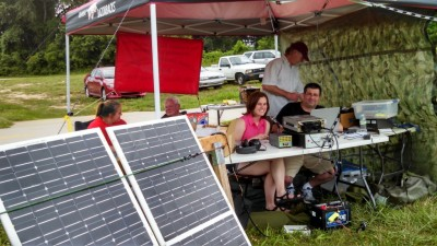 A view of the ARCUA Field Day 2014 site in which the solar panels and battery are visible. At the operating table are Hannah, KD5WNF and Mike, AE5ZC. Standing just behind the table is ARCUA faculty advisor Larry, WJ5V. Behind the panels are ARCUA student president Jill, AC0MX and Robert, KC0GHY. In front of the operating table you'll see the battery; the yellow box in front of the battery is a parametric PowerPole Breakout box in use!
