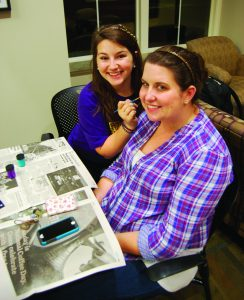 Junior Deanna Walker paints the face of senior Jenny Connor at the ADPi table.