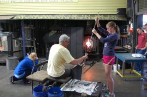 Bronwyn Gairing (left), Stephen Powell (center), and Cheyenne Evans (right), work on a project in the hot glass studio