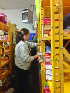 Senior Krissy Raque stocks shelves at the Catholic Action Center this past Saturday.