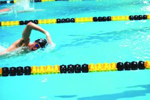 Senior Sam Walker swims freestyle during a race this season