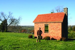 Centre graduate and professor Mark Lucas stands with his self-built cabin which was completed in the spring of 2013.