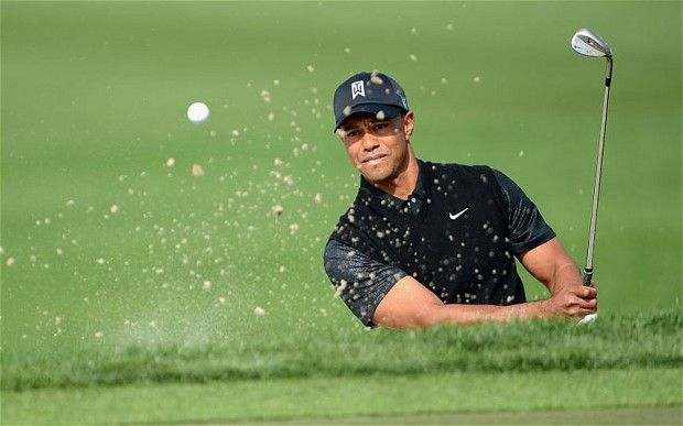 Tiger Woods plays a shot from the bunker and onto the green during a tournament in the 2013 PGA Tour. He looks to get back to form in 2014.