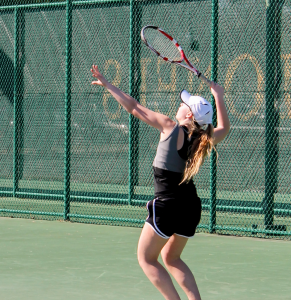 First-year Women's Tennis player Kate Tomey serves a shot over the net during action from a match earlier in the 2014 campaign