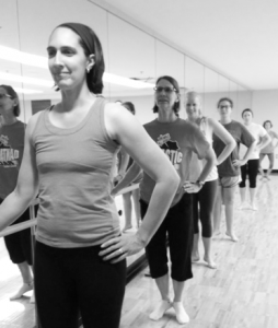 Settles leads a barre fitness class, mixing ballet dance techniques with yoga and pilatees.