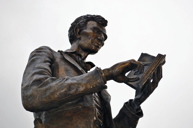 Sculpted by artist Ed Hamilton, the statue shows a young Abraham Lincoln steeped in study with the books belonging to John Todd Stuart.
