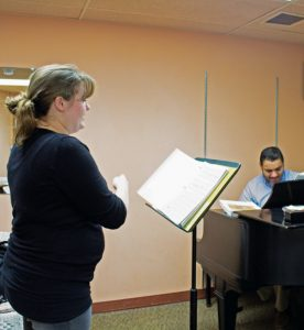 Sophomore Emilie O'Connor practices a piece with her voice teacher, Adjunct Professor of Music Mark Kano, in a Grant practice room.