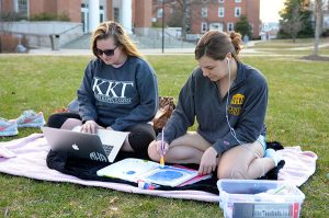 Pictured: Sophomores Meredith Harbison and Kelsie Essel Photo taken by Katherine Mackin Meredith Harbison and  Kelsie Essel take advantage of the warm spring weather to do homework on the lawn.