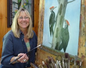 "Susan Parmenter in her studio painting ""Pileated Pair"""
