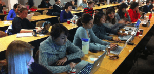 Participants actively learning software while sitting next to each other with their computers at long tables.