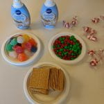 3 small plates arranged in a triangle, one filled with gumdrops, one of m&ms and one of graham crackers. Two bottles of frosting stand above the triangle and peppermint candies are scattered to their right.