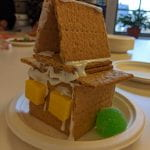 A tall gingerbread house with two yellow starbursts for windows and a green gumdrop on the side as if it was a bush.