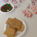 Graham crackers and red and green m&ms on two separate plates surrounded by warped peppermints and smarties