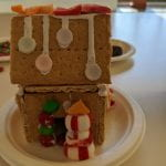 A gingerbread house with a door cut into it. Next to the door is a peppermint snowman with an orange starburst hat. Above the door, smarties decorate the roof.