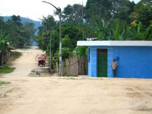 A man standing in front of a blue building on a dirt road.