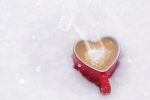 Heart shaped mug filled with steaming coffee sitting in the snow.