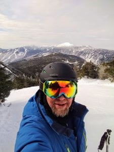 Chris taking a selfie at the top of a mountain before skiing down.