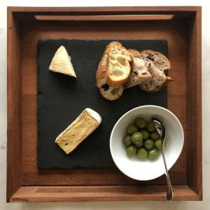 a plate or cheese, olives and slices of bread
