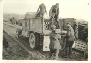Soldiers load lumber for field artillery positions into a supply truck.