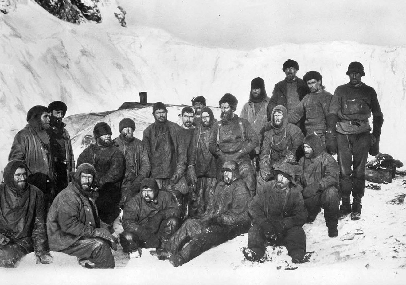 Twenty men standing on an icy island with thick snowsuit on.