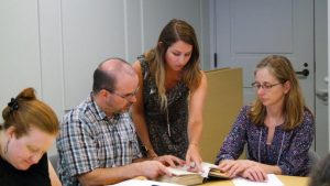 Four librarians examine a book.