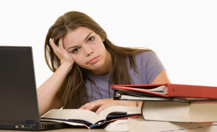 Young woman sitting in front of laptop beside a pile of thick textbooks while reading one with a frustrated stressed expression