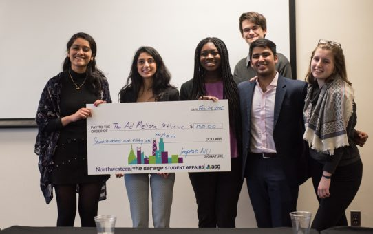 Winners of the Improve NU challenge holding their check