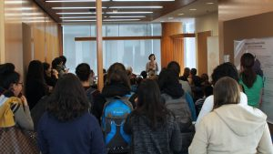 Neda Bagheri speaks to the standing room only crowd. Bagheri is a faculty member of the Chemistry of Life Processes Institute.