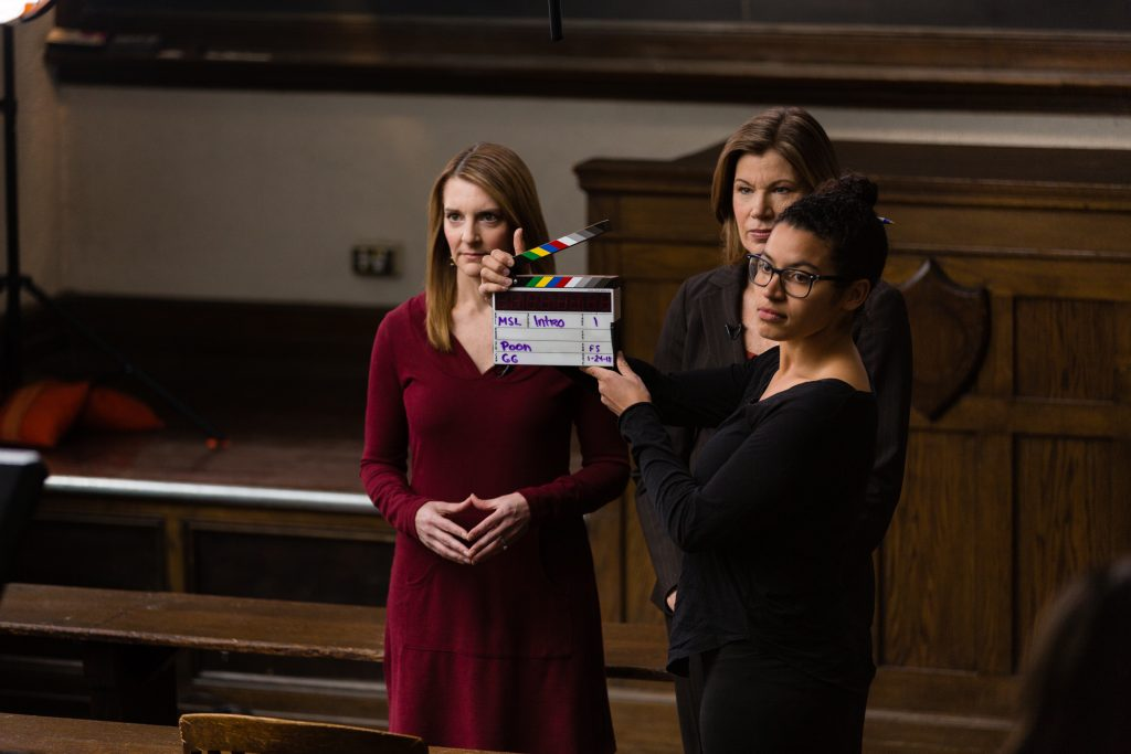 Woman with Clapperboard Stands in Front of Professors Sue Provenzano and Martha Kanter