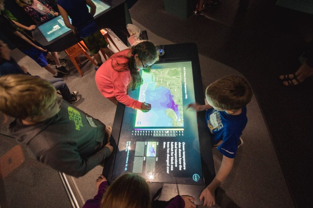 children interact with touchscreen map
