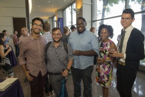 Image description: The photo is of the reception at the symposium. The main focus of the photo is five attendees standing in a line smiling and posing for the photo. In the background, other guests are milling about.
