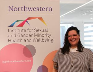 Eileen poses in front of ISGMH banner following their Current Issues in LGBTQ Health lecture.