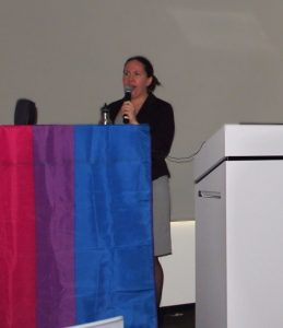 Dr. Lauren Beach speaks in front of podium covered with bisexual pride flag.