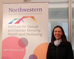Dr. Kirsten Simonton poses in from of a large ISGMH banner.