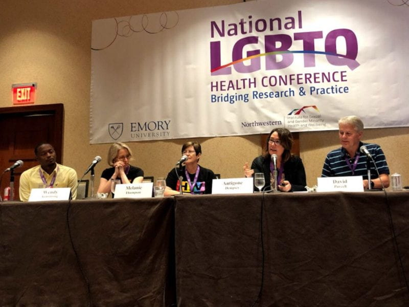 Five panelists sit at a table at the National LGBTQ Health Conference.