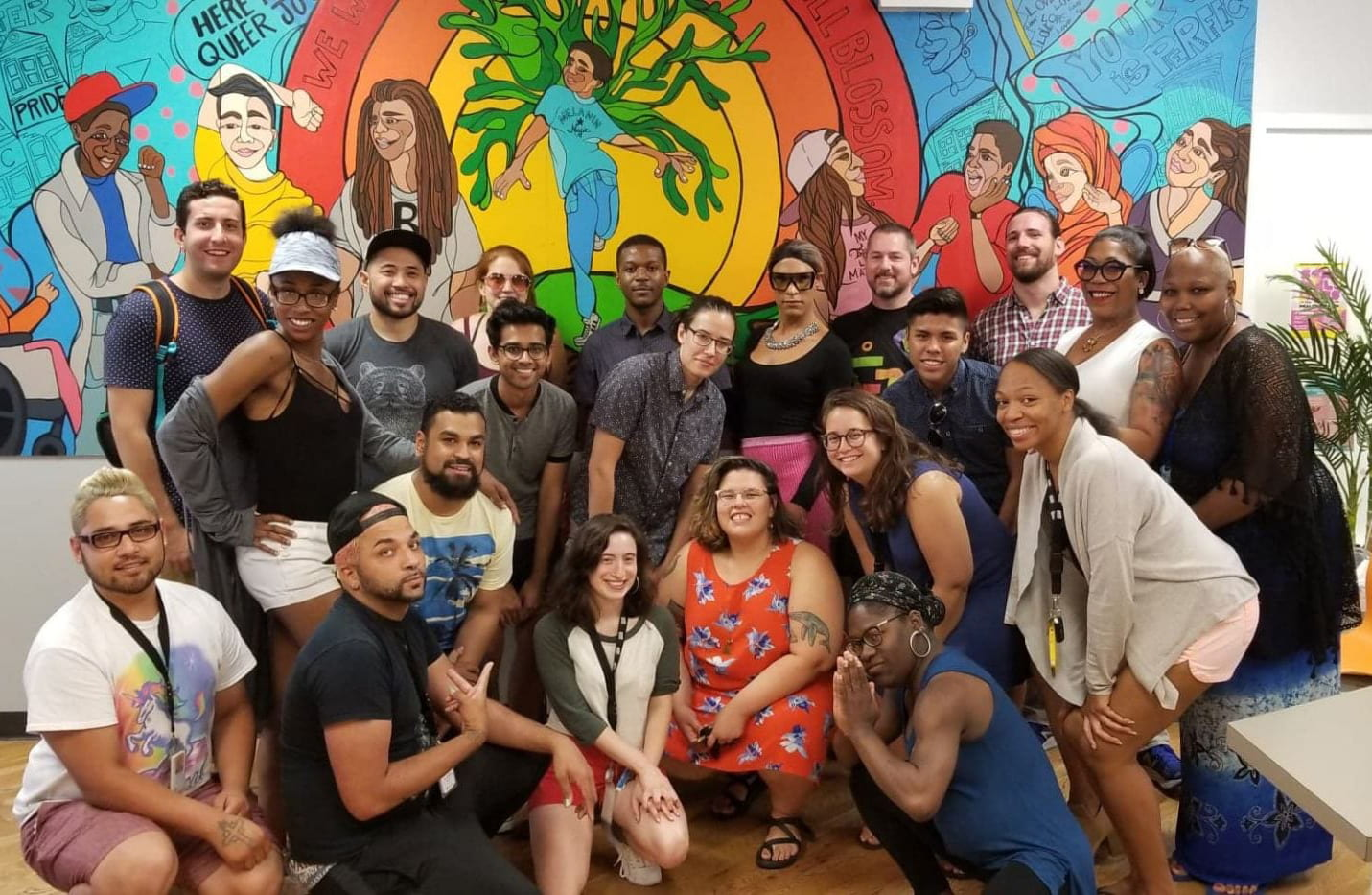 RADAR and Howard Brown Health Broadway Youth Center staff members pose in front of colorful mural