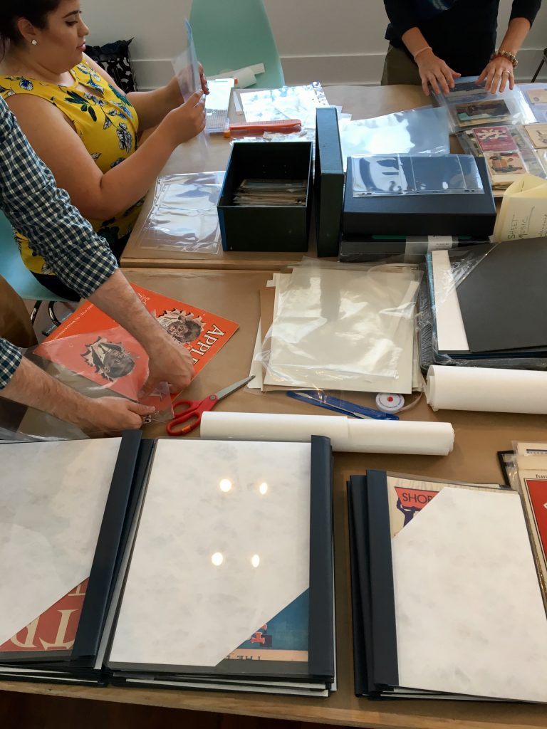 Volunteers rehousing sheet music and postcards