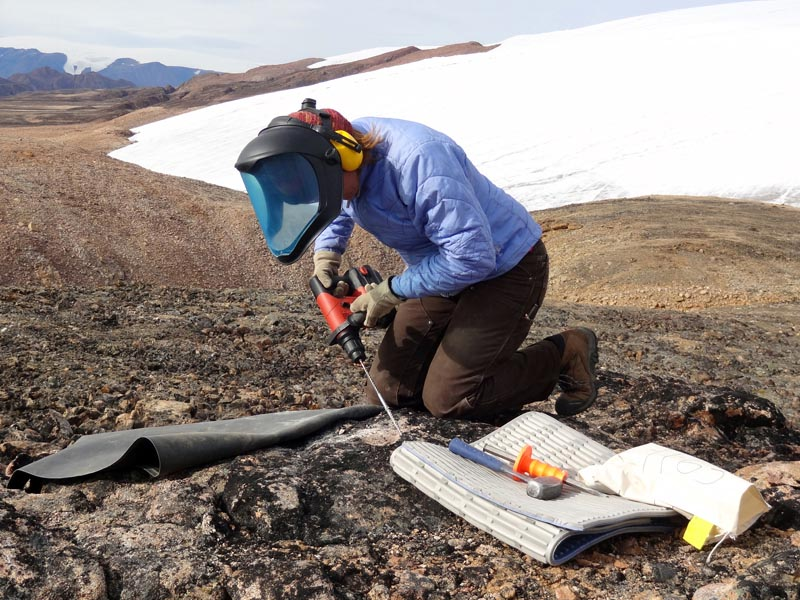Laura sampling a bedrock surface for cosmogenic surface exposure dating. Renland Ice Cap in background.