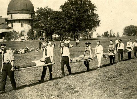 Photograph of Northwestern Ambulance Co. # 9 drill, May 1917 Taken on Northwestern's Evanston campus; Dearborn Observatory in the background.