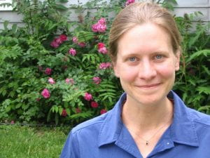 A photograph of Kate wearing a blue shirt and standing in front of flowers