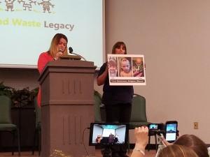 Meghan Beckerman speaks as Karen Nickels, co-founder of Just Moms STL, holds up photos of Beckerman's son.
