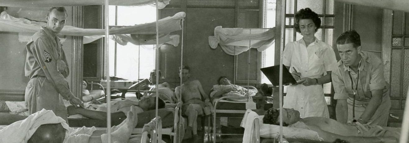 Patients lying in bed in an old seaside mansion during World War II.