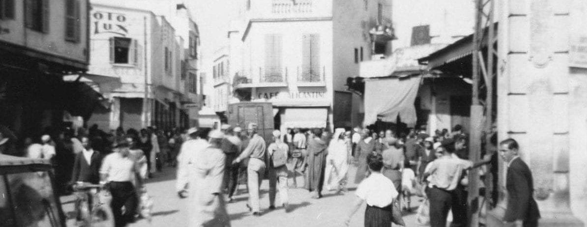 Bustling street with those in traditional dress, military uniforms, and French fashions of the 1940s