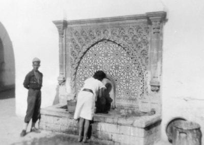Woman in a white dress bending over an ornate fountain