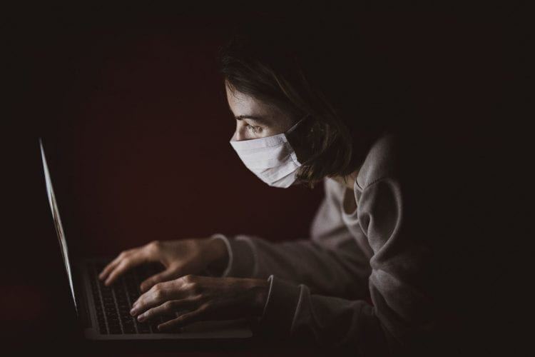 Masked researcher hunched over computer