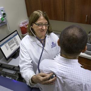 Nancy Klimas, M.D., co-principal investigator and director of Nova Southeastern University's College of Osteopathic Medicine's Institute for Neuro Immune Medicine, checks a patient's vital signs.